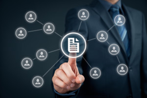 Corporate data management system (DMS) and document management system concept. Businessman click (or publish) on document connected with corporate users with access rights.